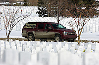 A vehicle carrying Bill and Terri Montag leads a procession of mourners past rows of headstones at Fort Logan National Cemetery in Denver on Thursday afternoon before a funeral for Terri's son, Eric O'Hara.