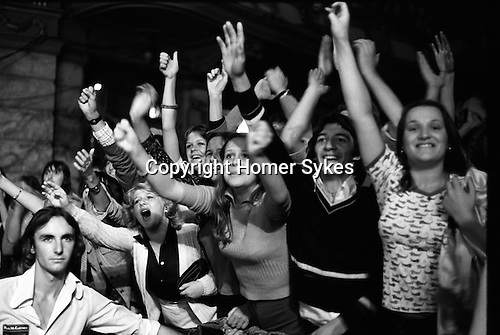 """Paul and Linda McCartney Wings Tour 1975.  Ecstatic female fans scream and wave their arms, an impassive bouncer stands at their side. Bristol, England. The photographs from this set were taken in 1975. I was on tour with them for a children's """"Fact Book"""". This book was called, The Facts about a Pop Group Featuring Wings. Introduced by Paul McCartney, published by G.Whizzard. They had recently recorded albums, Wildlife, Red Rose Speedway, Band on the Run and Venus and Mars. I believe it was the English leg of Wings Over the World tour. But as I recall they were promoting,  Band on the Run and Venus and Mars in particular."""