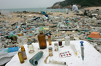 Medical waste is seen the East-facing beach on the windward side of South Sokos Island, Hong Kong, China, 27 January 2010. South Sokos Island is one of a very small number of uninhabited islands in Hong Kong Special Administrative Region of China, and because it has no ferry service at all it is rarely visited by anyone. Consequently large amounts of marine-borne plastics build-up over time, with infrequent Hong Kong Government pollution clean-up efforts to tackle the problem. Common items found washed up on the beach at South Sokos Island include; lightbulbs, medical waste, plastic bottles, plastic cigarette lighters, plastic toys, plastic fishing equipment and plastic footwear. Another plastic item frequently found in large quantities on Soko Island, but also on polluted beaches the world over, is the pre-production plastic pellet, or 'nurdle', that is used in the manufacturing of plastic products. ALEX HOFFORD