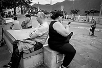 """Switzerland. Canton Ticino. Lugano. Town Center. A couple sits and rest. The man is half asleep and the woman checks the latest news on her mobile phone. The safety sanitary measures advocate people to stand apart in order to avoid close contact and potential contamination by coronavirus. Due to the spread of Coronavirus (also called Covid-19), the Federal Council has categorised the situation in the country as """"extraordinary"""". It has issued a recommendation to all citizens to stay at home, especially the sick and the elderly. From March 16 the government ramped up its response to the widening pandemic, ordering the closure of bars, restaurants, sports facilities and cultural spaces. Lake Lugano (Italian: Lago di Lugano or Ceresio) is a glacial lake which is situated on the border between southern Switzerland and Northern Italy. 10.05.2020 © 2020 Didier Ruef"""