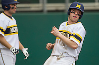 Michigan Wolverines shortstop Travis Maezes (9) scores during the NCAA baseball game against the Washington Huskies on February 16, 2014 at Bobcat Ballpark in San Marcos, Texas. The game went eight innings, before travel curfew ended the contest in a 7-7 tie. (Andrew Woolley/Four Seam Images)