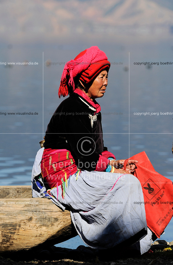 CHINA Yunnan Lugu Lake , ethnic minority Mosuo who are buddhist and women have a matriarch / CHINA Provinz Yunnan , Frau mit pearkboy tasche die chinesische Variante von Playboy, ethnische Minderheit Mosuo am Lugu See , die Mosuo sind Buddhisten und Mosuo Frauen ueben ein Matriarchat aus