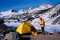 A hiker sets his tent as he makes camp on a crystal clear day in the high Sierras. South Lake, King's Canyon National Park, California.