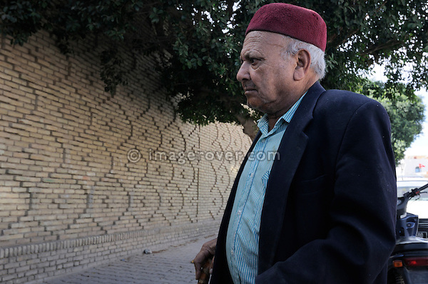 Africa, Tunisia, Tozeur. Local tunisian man wearing a typical hat in Tozeur's old quarter. --- No releases available, but releases may not be needed for certain uses. --- Info: Tozeur, and the Jerid region, is very famous for its yellow/brownish brick architecture as well as its fascinating patterns in simple and rich geometric designs form the façades of most buildings in the old city/medina. --- Info: Image belongs to a series of photographs taken on a journey to southern Tunisia in North Africa in October 2010. The trip was undertaken by 10 people driving 5 historic Series Land Rover vehicles from the 1960's and 1970's. Most of the journey's time was spent in the Sahara desert, especially in the area around Douz, Tembaine, Ksar Ghilane on the eastern edge of the Grand Erg Oriental.