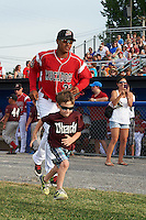 """Batavia Muckdogs left fielder Jhonny Santos (32) takes the field with a young """"Stars of the Game"""" participant before a game against the Brooklyn Cyclones on July 4, 2016 at Dwyer Stadium in Batavia, New York.  Brooklyn defeated Batavia 5-1.  (Mike Janes/Four Seam Images)"""