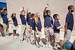 Elementary age mixed race children in uniforms line up outside of school  holding hands up in New Orleans, Louisiana