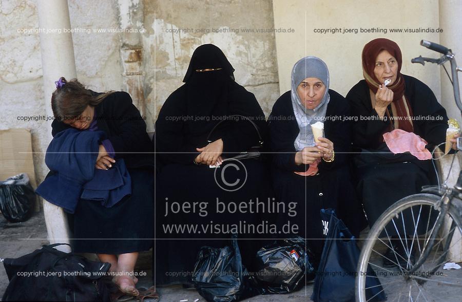 SYRIA, veiled Muslim women eat ice cream at Umayad mosque in Damascus / Syrien Damaskus Damascus schwarz verschleierte Moslem Frauen im Tschador essen Eis an der Omayad Moschee