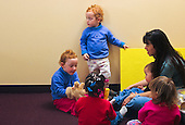 MR / Schenectady, New York. Schenectady Day Nursery (private nonprofit daycare center). Toddler class. Teacher (Chinese-American and Caucasian) and students (aged 18 - 30 months)  do language development activity together. One student is at the edge of the group, not paying attention. ID: SDNT ©Ellen B. Senisi