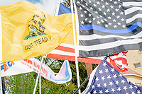 """A variety of flags, including an American Flag, a Gadsden Flag, and a """"Blue Lives Matter"""" flag are seen on the stage as people gather for an anti-lockdown protest organized by the alt-right group Super Happy Fun America near the home of Massachusetts governor Charlie Baker in Swampscott, Massachusetts, on Sat., May 16, 2020. The protest was in defiance of Massachusetts orders mandating face coverings and social distancing and prohibiting gatherings larger than 10 people during the ongoing Coronavirus (COVID-19) global pandemic. The state's stay-at-home order is expected to be updated on May 18, 2020, with a phased reopening plan issued by the governor as COVID-19 cases continue to decrease. Anti-lockdown protests such as this have become a conservative cause and have been celebrated by US president Donald Trump. Many of the protestors displayed pro-Trump messages or wore Trump campaign hats and shirts with phrases including """"Trump 2020"""" and """"Keep America Great."""" Super Happy Fun America, organizers of the protest, are an alt-right organization best known for creating the 2019 Boston Straight Pride Parade."""