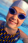 portrait of smiling young girl in pool wearing swim googles and cap