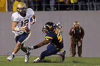 Pitt quarterback Tino Sunseri (12) eludes a tackle by WVU linebacker Najee Goode. The WVU Mountaineers beat the Pitt Panthers 21-20 at Mountaineer Field in Morgantown, West Virginia on November 25, 2011.
