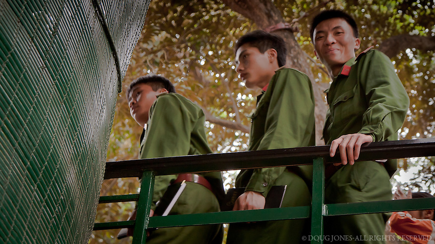 Hundreds-thousands of people each day wait for over an hour for a brief glimpse into Ho Chi Minh's modest presidential residence in Hanoi.  These soldiers are happy that their wait is almost over.