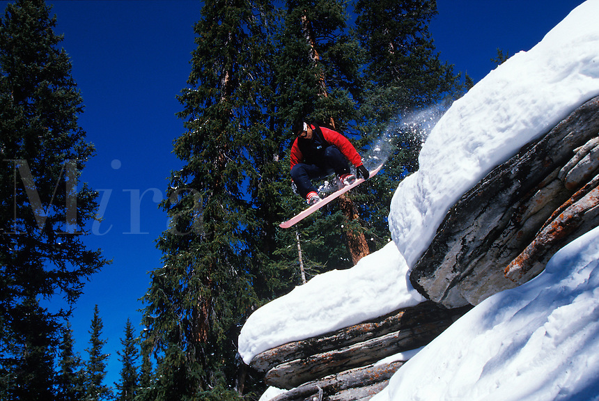 Snowboarder jumping a cliff.