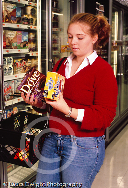 College student female shopping at supermarket, in frozen food section, reading labels on packages