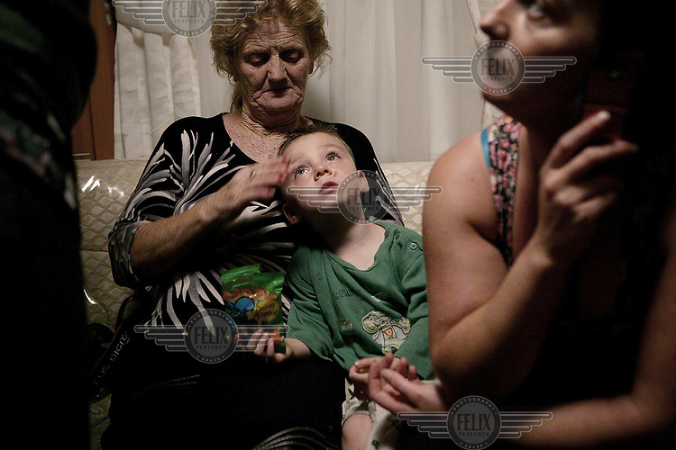 Richard Sheridan sits with his mother Jean and grandmother Jeany in his family's trailer at Dale Farm, an Irish Travellers' site on a former scrapyard in Essex.