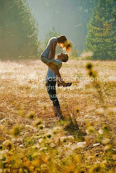 Young couple in field, woman held aloft