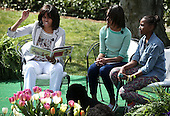"""First lady Michelle Obama (L) reads the story """"Cloudy with a Chance of Meatballs"""" to children as daughters Sasha (R) and Malia (2nd L) look on during the annual White House Easter Egg Roll on the South Lawn of the White House April 1, 2013 in Washington, DC.  President Barack Obama and first lady Michelle Obama hosted thousands of people during the annual celebration of Easter.  .Credit: Alex Wong / Pool via CNP"""