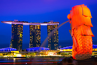 Merlion statue fountain lit up in orange at twilight, with Marina Bay Sand hotel in the background in Merlion Park, Singapore Southeast Asia