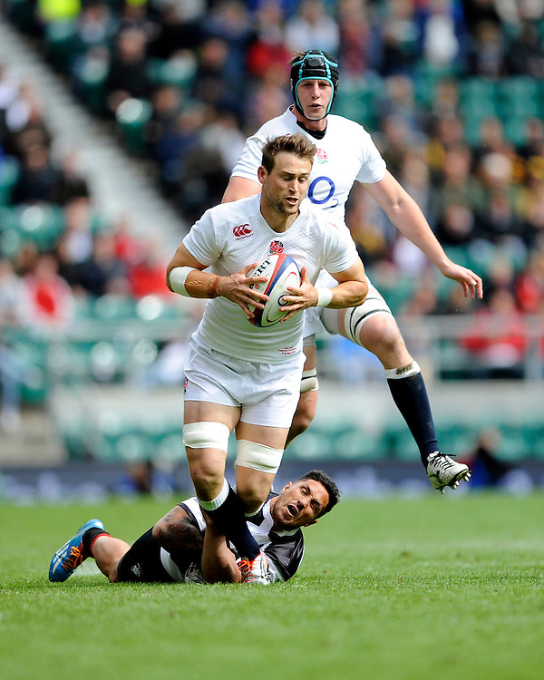 Jon Fisher of England is tackled by George Smith of Barbarians during the match between England and Barbarians at Twickenham Stadium on Sunday 31st May 2015 (Photo by Rob Munro)
