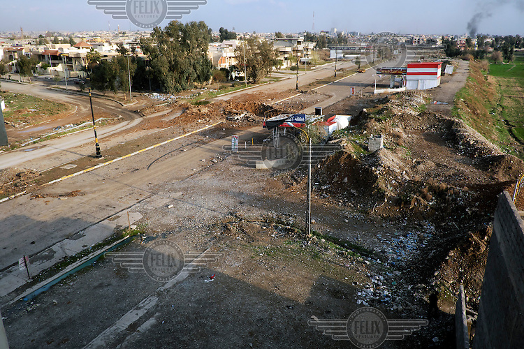 An ordinance crater in the middle of a road in the Hay Ba'th  neighbourhood, near the Tigris River.