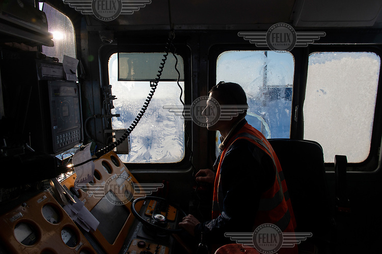 Engineer Alexander Mironovich in the driver's cab of a locomotive on the Obskaya-Bovanenkovo railway that links the Gasprom Bovanenkovo gas field to the outside world.