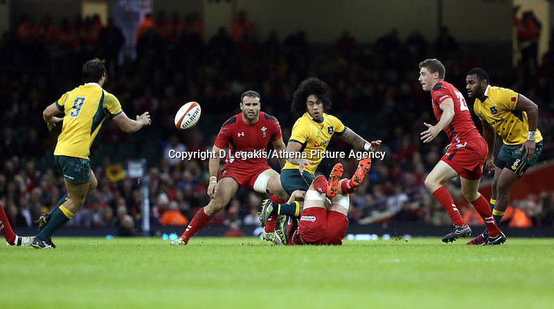 Pictured: Joe Tomane of Australia (3rd L) passing the ball to team mate Nick Phipps (L) Saturday 08 November 2014<br /> Re: Dove Men Series rugby, Wales v Australia at the Millennium Stadium, Cardiff, south Wales, UK.