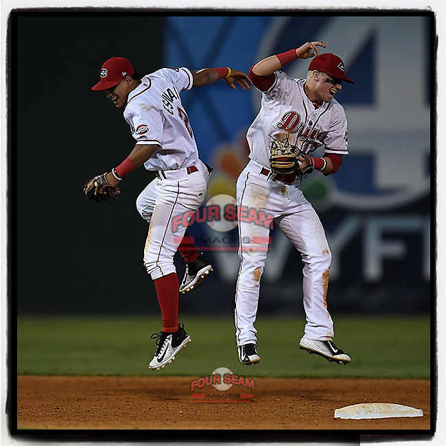 Shortstop Santiago Espinal (2) and second baseman Brett Netzer (12) of the Greenville Drive celebrate the win in Game 3 of the South Atlantic League Southern Division Playoff against the Charleston RiverDogs on Saturday, September 9, 2017, at Fluor Field at the West End in Greenville, South Carolina. Greenville won, 5-0, winning the division championship two games to one. (Tom Priddy/Four Seam Images)
