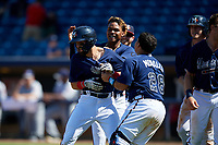 Mississippi Braves Alejandro Salazar (48) is congratulated by Cristian Pache (16) and Jonathan Morales (28) after laying down a bunt for a walk-off squeeze play during a Southern League game against the Jacksonville Jumbo Shrimp on May 5, 2019 at Trustmark Park in Pearl, Mississippi.  Mississippi defeated Jacksonville 1-0 in ten innings.  (Mike Janes/Four Seam Images)