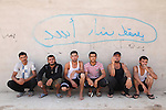 DOMIZ, IRAQ: Syrian refugees sit in the shade outside a mosque in the Domiz refugee camp where they are living...Over 7,000 Syrian Kurds have fled the violence in Syria and are living in the Domiz refugee camp in the semi-autonomous region of Iraqi Kurdistan...Photo by Ari Jalal/Metrography