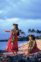 Two young women dancing kahiko (ancient) hula wearing maile leis with ipu (gourd) near ocean