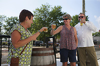 Karen Stadie (from left), Tami Varlik and Gary Varlik of Lincoln, Neb. toast, Friday, July 23, 2021 at Ozark Beer Company in Rogers. They expanded their patio area and added to their capacity. The brewery is in downtown Rogers and was the second largest beer producer in the state in 2019. Check out nwaonline.com/210724Daily/ for today's photo gallery. <br /> (NWA Democrat-Gazette/Charlie Kaijo)