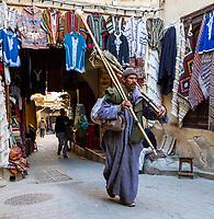 Fes, Morocco.  Broom Salesman, a Street Scene in the Medina.