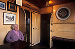 """The Village Pub. The Drewe Arms. Drewsteignton, Devon, England. Interior portrait of publican Mabel Mudge. Local would go to their ale house, to """"Aunty Mabel's for a drink."""" In 1991 she was England's oldest landlady and in her nineties. She had lived in the pub since 1919 and holds court in the bar, remembering customers arriving by horse and cart. When her artillerist is bad she invites you to draw your own glass of ale or cider from the  casks stillaged behind the servery. 1990s 1991"""