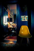 A retro yellow stands in the corner of a blue hallway with a view through an open door to a room beyond