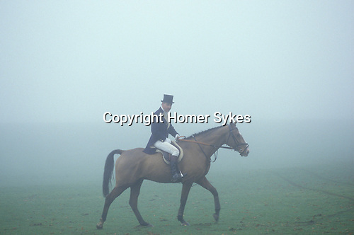 Badminton, Gloucestershire. 1985<br /> In his black silk top hat, and wearing the traditional distinive Blue and Buff, the colours of the Duke of Beaufort Hunt, a  subscribers walks his horse back across the Badminton Park. Huntsmen  and Whippers-In wear green.