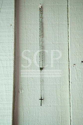 Fazenda Bauplatz, Brazil. Rosary with cross hanging on a nail on a painted wooden wall.