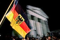 DEUTSCHLAND, 03.10.90.Berlin - Mitte.Feiern zur deutschen Wiedervereinigung:.Fahnenschwinger auf dem Pariser Platz am Brandenburger Tor.© Martin Fejér