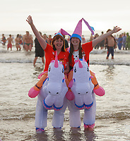 Pictured: Two women in unicorn costumes. Wednesday 25 December 2019<br /> Re: Hundreds of people in fancy dress, have taken part in this year's Porthcawl Christmas Swim in south Wales, UK.