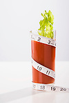 Tape measure wrapped around glass of tomato juice with celery stalk