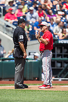 North Carolina State Wolfpack head coach Elliott Avent argues a call with home plate umpire Joe Burleson during Game 3 of the 2013 Men's College World Series between the North Carolina State Wolfpack and North Carolina Tar Heels at TD Ameritrade Park on June 16, 2013 in Omaha, Nebraska. The Wolfpack defeated the Tar Heels 8-1. (Brace Hemmelgarn/Four Seam Images)