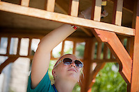 """Lauren Herneisey applies wood stain to a gazebo during """"Circle the City with Service,"""" the Kiwanis Circle K International's 2015 Large Scale Service Project, on Wednesday, June 24, 2015, in Indianapolis. (Photo by James Brosher)"""