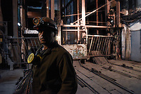 Ukrainian coal miner waits in front of mine elevator before going underground to help search for bodies of colleagues and clear up debris following an explosion at the Zasyadko mine in Donetsk, Ukraine, Wednesday, March 4, 2015.