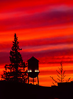 A fine art landscape image of a traditional water tower at sunset, a black silhouette against a crimson sky.