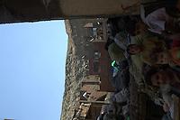 2011 Mokattam Garbage City (alla periferia del Cairo) il quartiere copto dove si vive in mezzo alla spazzatura raccolta: una donna e alcuni bambini tra i sacchi dell'immondizia. Sullo sfondo case nuove in costruzione e in fianco della montagna.