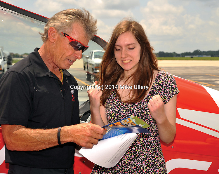 """Albarta Dempsey, 15, of Centerville, reacts to learning about some of the programs and benefits associated with being a part of the EAA Young Eagles Program, prior to her flight with aviation legend Seans D. Tucker at the Dayton International Airport on Wednesday. Miss Alberta Dempsey, 15, of Centerville takes a Young Eagles flight with National Chairman Sean D. Tucker at the Dayton International Airport on June 25, 2014. Dempsey wrote an essay that was chosen as the best of all entrants from around the Dayton area to earn her ride with National Aviation Hall of Famer, and air show legend Sean D. Tucker. The Young Eagles program is part of the Experimental Aircraft Association for which Tucker serves as national chairman. The EAA's Young Eagles program has given a first flight to nearly 2 million kids. All pilots associated with the program are volunteers.Tucker said that it was an honor to be the person to give a Young Eagles flight to Dempsey, whom he described as bright and intelligent. Once back on the ground, Dempsey said that her flight was """"amazing."""""""