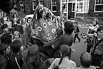 """Minehead Hobby Horse Somerset. UK.  """"Booting"""" ceremony in the centre of town on last evening. A boy, a  young person is held out in front of the Hobby Horse and struck 10 times by the bow of the Hobby Horse.<br /> <br />  My ref 27a/958/1975"""