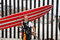 """Tom Jones carries his 14ft paddleboard away from the US Mexico border at Border Field State Park, the south-western most corner of the contiguous United States, Friday, November 9, 2007.  Jones became the first person to paddle the entire 1250-mile coast of the California on a paddleboard when his three and a half month long journey ended at the border fence in southern San Diego.  The expedition, called """"California Paddle 2007"""" was designed to draw attention to the problem of plastic pollution in the world?s oceans and its detrimental effect on marine life. (Photo Ronan Gray)"""