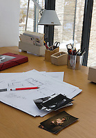 A selection of floor plans and photographs is displayed on a contemporary desk top