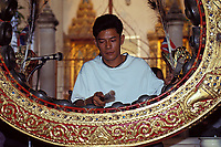 musician plays traditional instrument at temple, Bankok, Thailand
