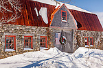 A snow-caped stone barn with flag and wreath in Bar Harbor, ME, USA
